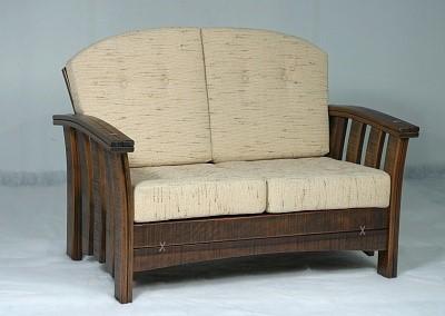 Двухместный диван из массива дерева с мягкими подушками, которые легко убрать в помещение при дождливой погоде.