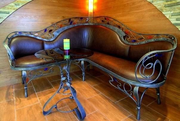 Угловой кованый диван станет главным украшением беседки, а столик, выполненный в том же стиле, придаст законченность всему интерьеру.