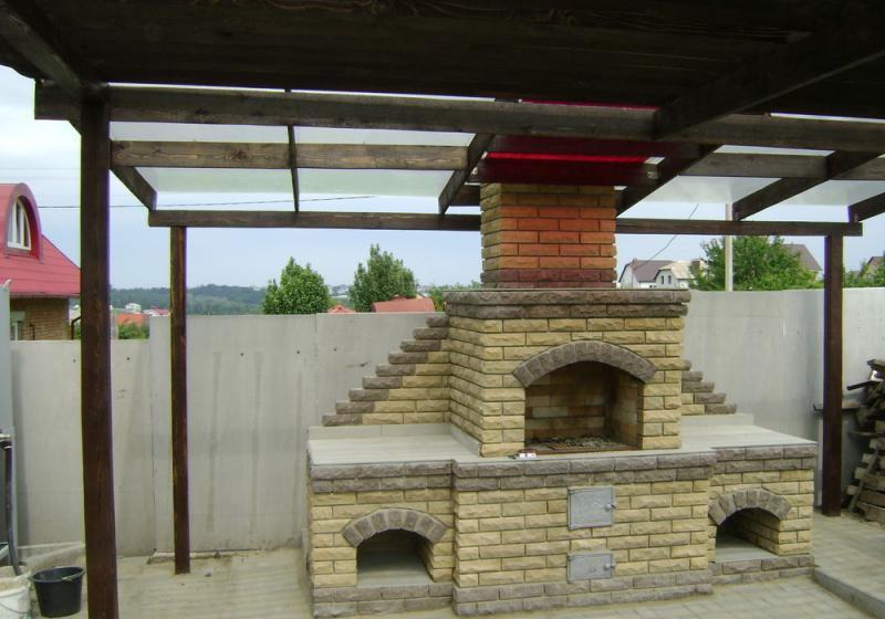 Открытая веранда с мангалом из кирпича, нишами под дрова и местами для приготовления пищи.