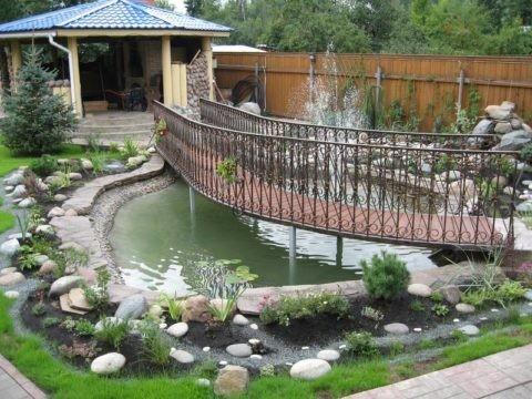 Мостик, перекинутый через искусственный водоем и ведущий к беседке, создает иллюзию островного расположения строения