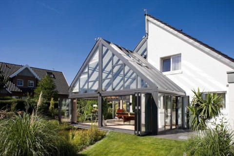 Остекленная конструкция крыши веранды повторяет конфигурацию кровли здания