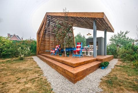 В беседке сочетаются деревянное основание, металлические столбы и кирпичная кладка под кухонную зону