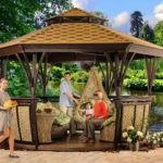 Полуоткрытая беседка у пруда с плетеными стенками и мебелью