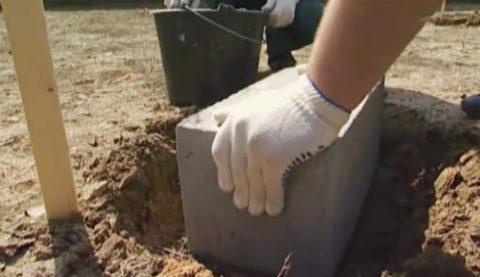 Уложите в подготовленные лунки бетонные блоки