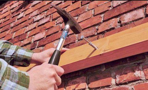 Закрепите балку на стене дюбелями