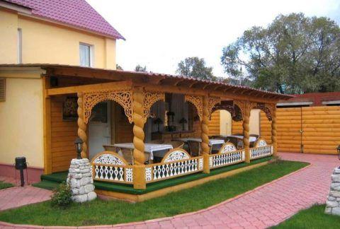 Резная деревянная пристройка хорошо сочетается со стилистикой участка